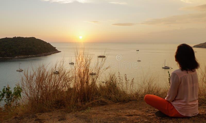 La ragazza che si siede nella posizione di meditazione del loto di yoga nella parte anteriore alla spiaggia sulle rocce una sorve fotografia stock