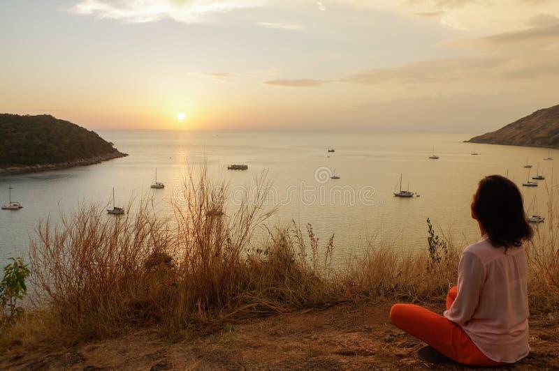 La ragazza che si siede nella posizione di meditazione del loto di yoga nella parte anteriore alla spiaggia sulle rocce una sorve fotografia stock libera da diritti