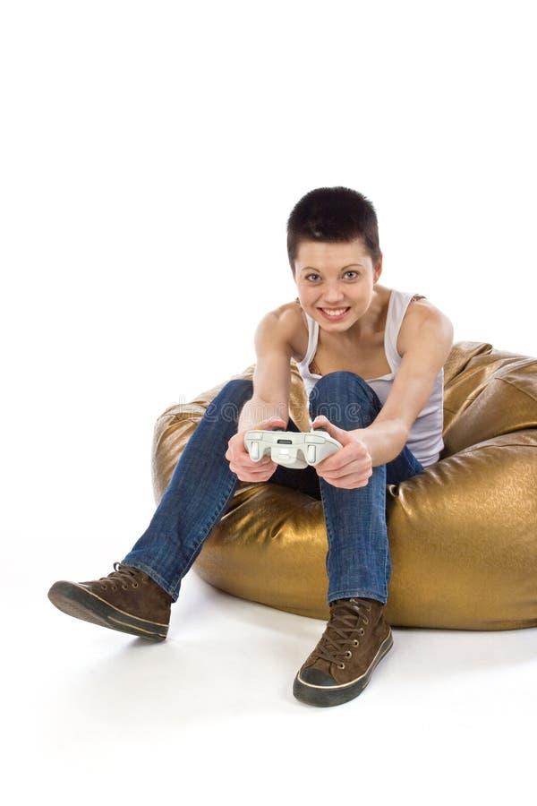 La ragazza che si siede su un sacchetto gioca il video gioco fotografia stock libera da diritti