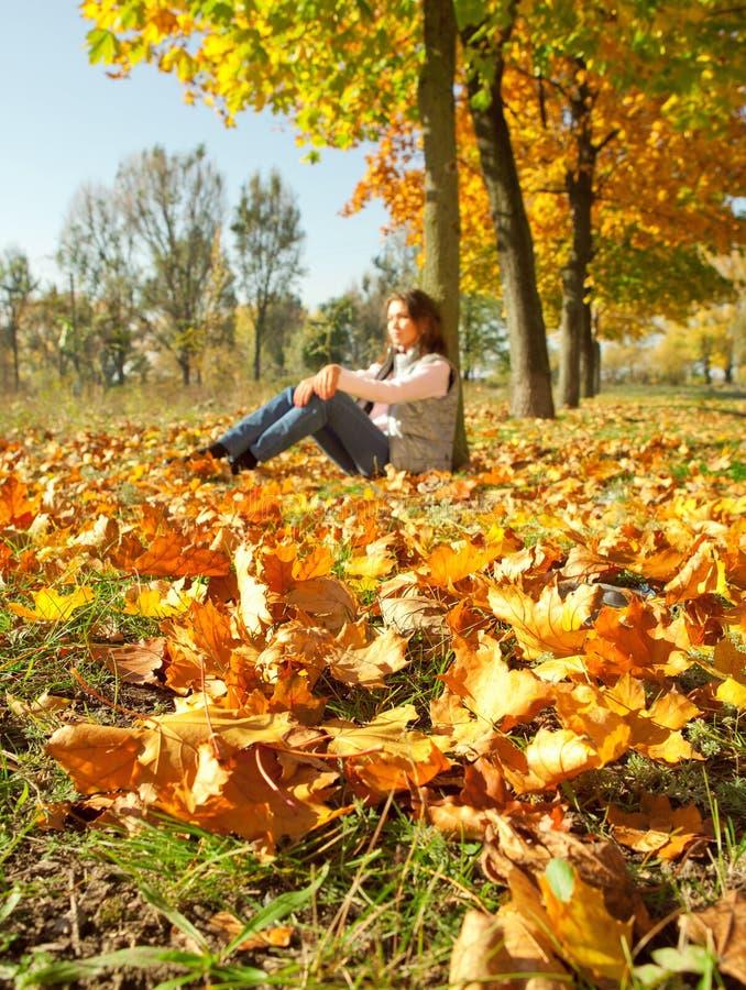 La ragazza che si siede sul colore giallo lascia la moquette fotografia stock libera da diritti