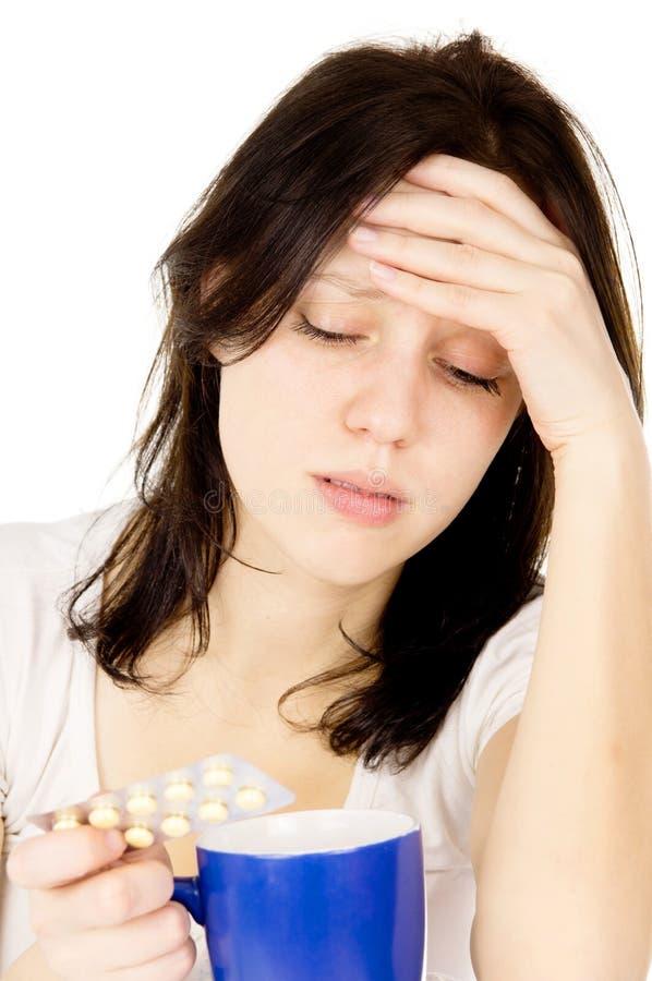 La ragazza che si siede sul letto e su una testa molto irritata fotografia stock