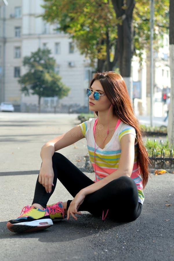 La ragazza che si siede sul marciapiede si è vestita in vestiti di sport immagini stock libere da diritti