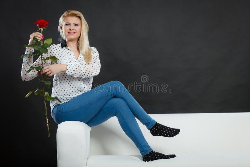 La ragazza che si siede sul sofà tiene la rosa rossa, su buio fotografia stock
