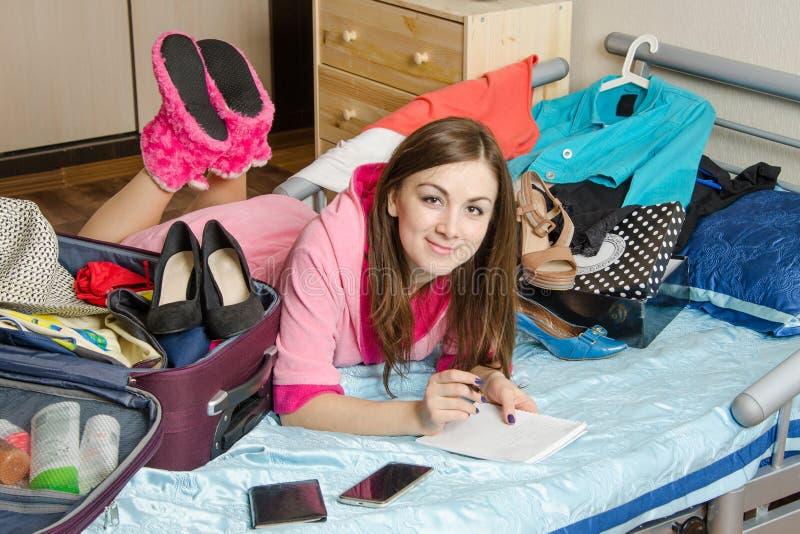 La ragazza che si trova sul letto è una lista delle cose in vacanza immagine stock libera da diritti