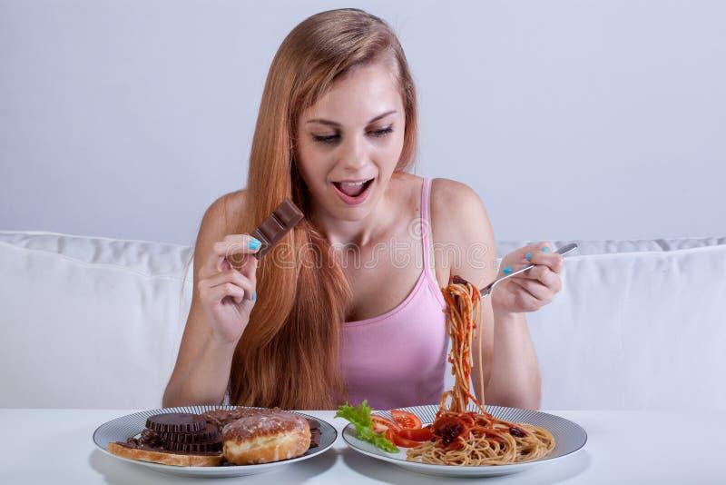 La ragazza che soffre dalla bulimia mangia la cena fotografia stock libera da diritti