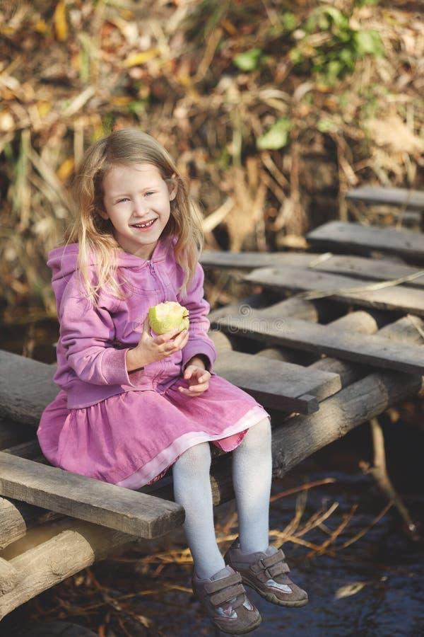 La ragazza che sorride e che mangia la mela in autunno sulla natura cammina all'aperto fotografie stock