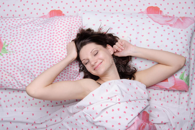 La ragazza che sveglia a letto allunga felicemente immagini stock