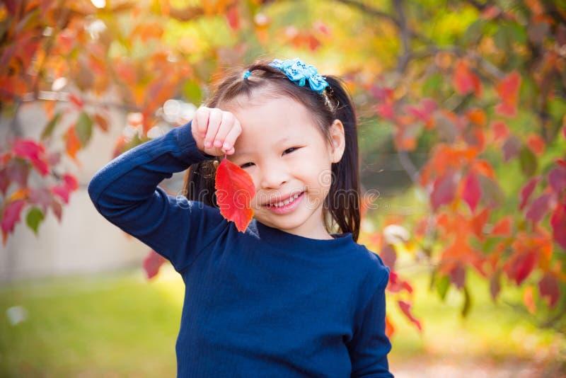 La ragazza che tengono la foglia di colore rosso ed il sorriso in autunno parcheggiano immagini stock