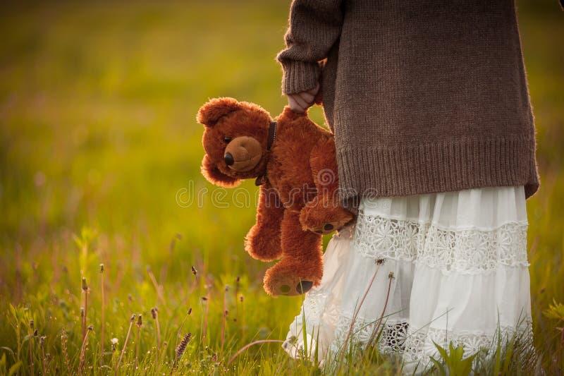 La ragazza che tiene l'orsacchiotto marrone disponibile riguarda il campo di mattina fotografie stock libere da diritti