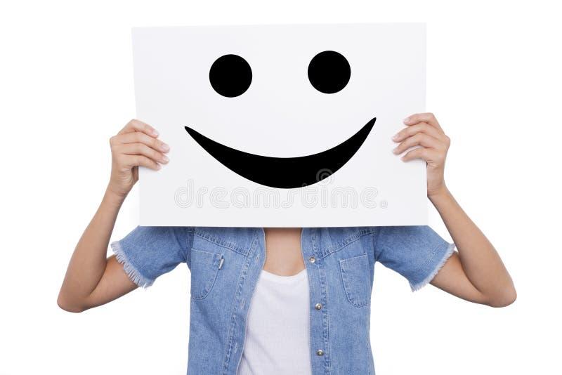 La ragazza che tiene un cartello con sorridere sorride parte anteriore del suo fronte fotografia stock