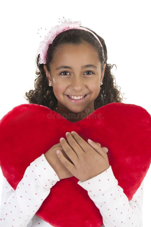 La ragazza che tiene un cuore ha modellato il cuscino in sue braccia fotografia stock libera da diritti