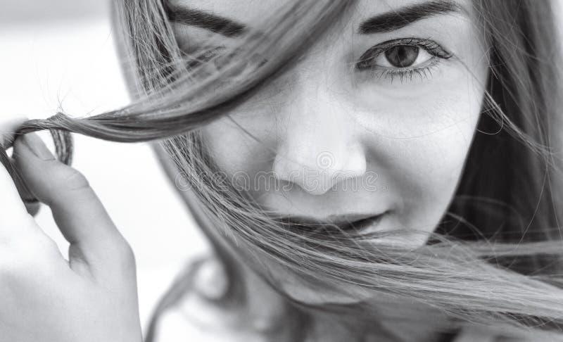 La ragazza che tiene un mèche di capelli e esamina la macchina fotografica Fine-u fotografia stock