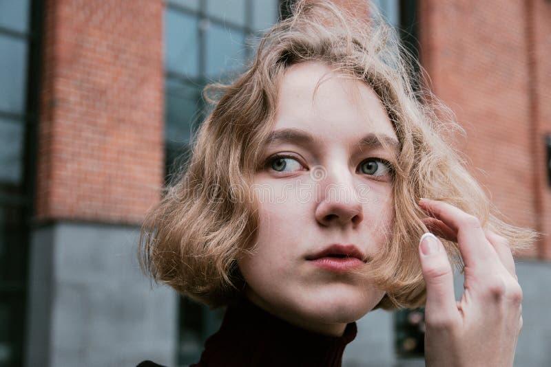 La ragazza che tiene un mèche di capelli, si chiude sul ritratto immagini stock libere da diritti