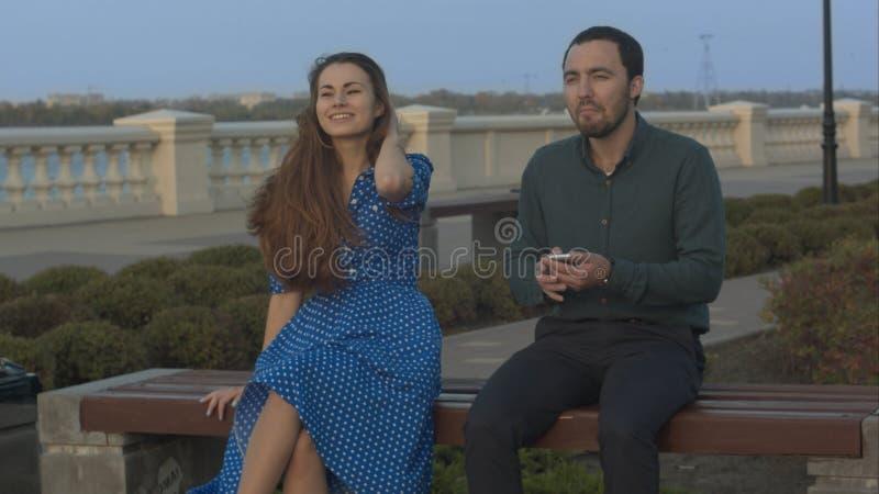 La ragazza chiede all'uomo di smettere di per mezzo dello smartphone fotografia stock