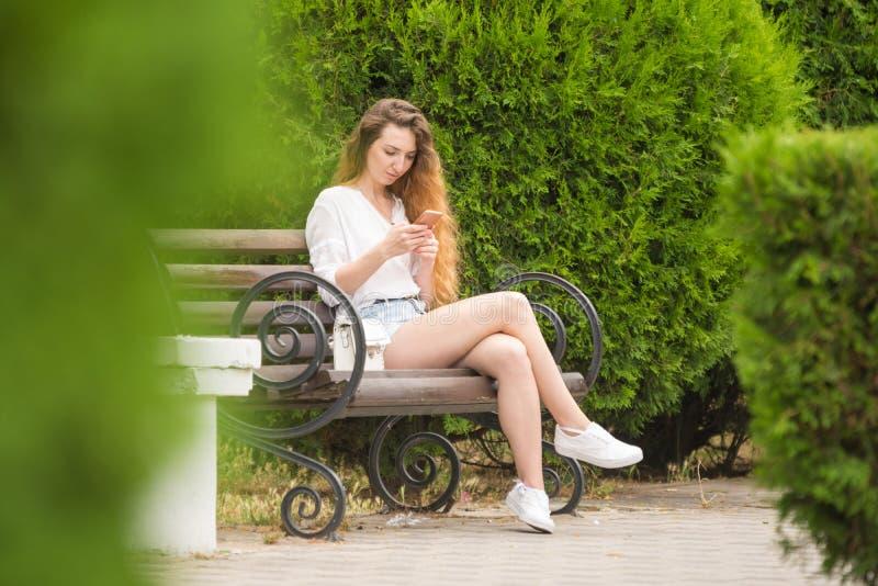 La ragazza comunica nelle reti sociali che si siedono su un banco di parco immagini stock libere da diritti