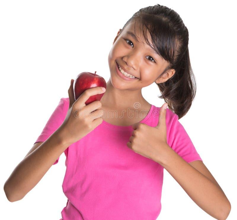 La ragazza con Apple ed i pollici aumentano il segno V immagine stock
