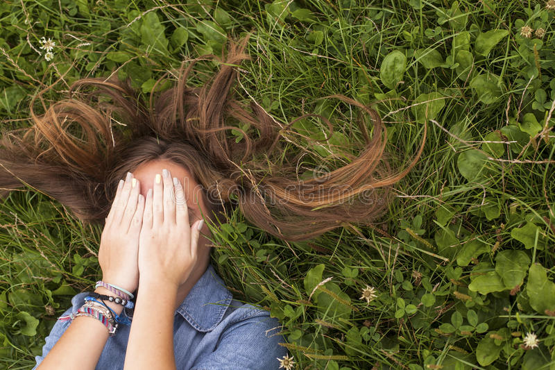 La ragazza con capelli lunghi, chiudentesi osserva mentre si trova nell'erba verde distendasi immagine stock