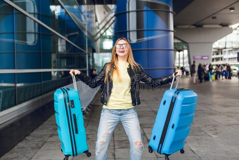 La ragazza con capelli lunghi in vetri sta tenendo due valigie blu fuori in AirPort Porta il maglione giallo, rivestimento fotografia stock libera da diritti