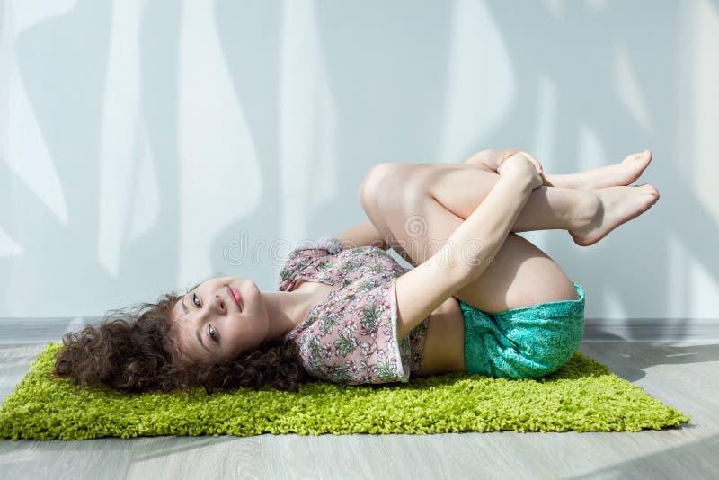 La ragazza con capelli ricci che si trovano sul pavimento, fa l'allungamento degli esercizi fotografia stock