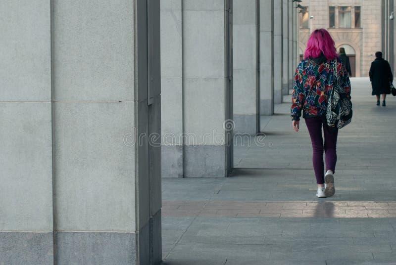 La ragazza con capelli rosa che cammina lungo le alte colonne concrete, una donna in un ambiente urbano immagine stock libera da diritti