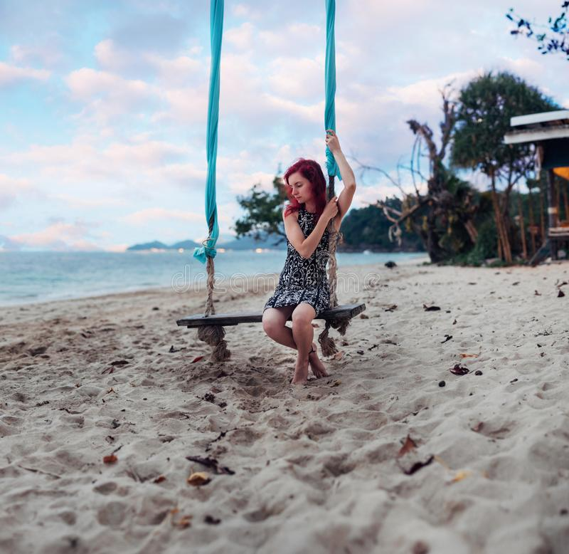 La ragazza con capelli rossi sta rilassandosi su oscillazione al sulla spiaggia immagini stock libere da diritti