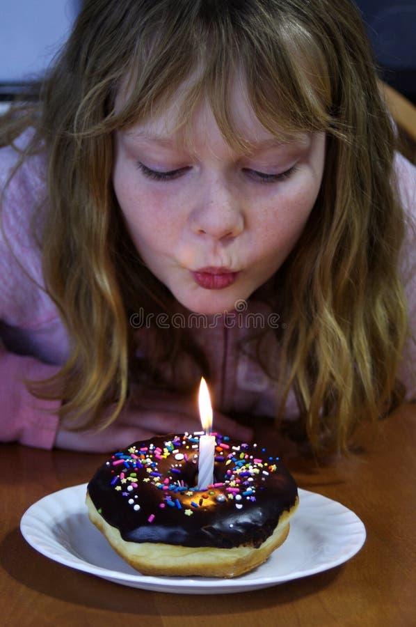 La ragazza con la ciambella del cioccolato con spruzza e la candela di compleanno fotografia stock