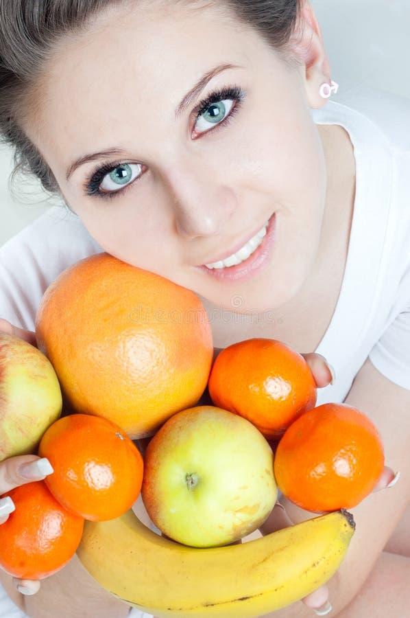 La ragazza con frutta in mani fotografia stock