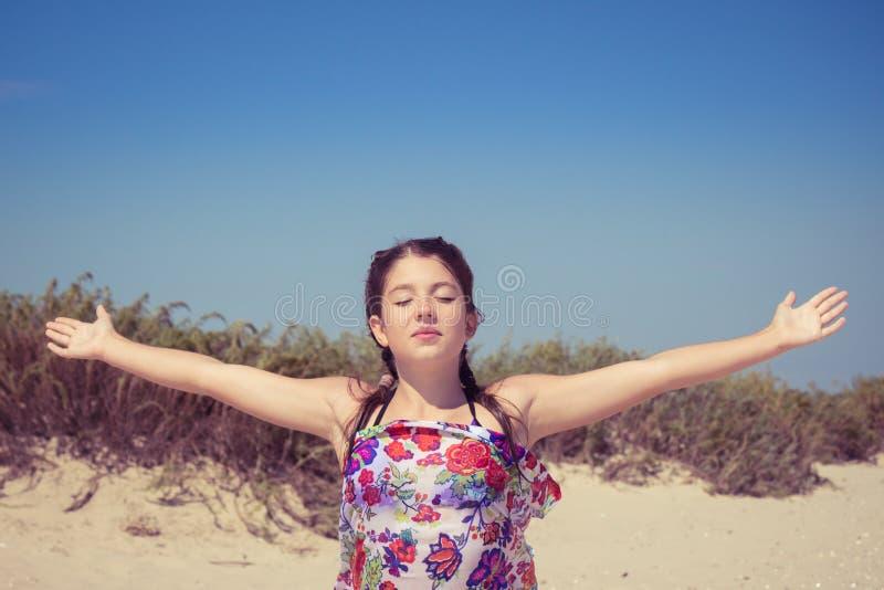La ragazza con gli occhi ha chiuso godere del sole e del vento fotografie stock