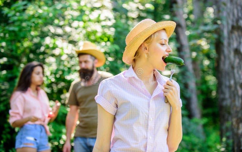 La ragazza con grande appetito mangia l'alimento arrostito Amici che mangiano picnic dell'alimento Uomo che alimenta signora affa fotografia stock