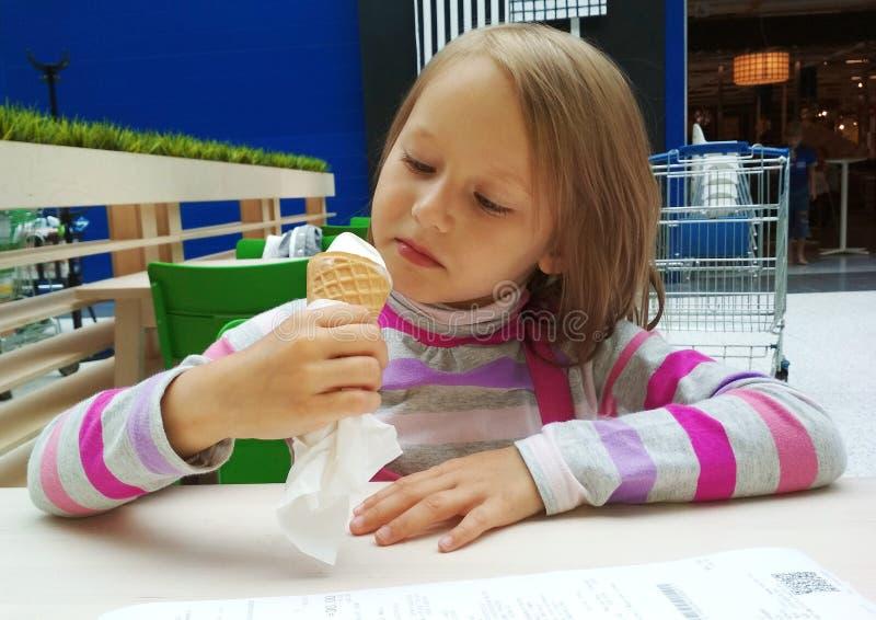La ragazza con i capelli lunghi biondi mangia il gelato nel deposito in alimenti a rapida preparazione immagini stock libere da diritti