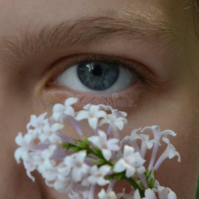 La ragazza con i fiori osserva fotografia stock