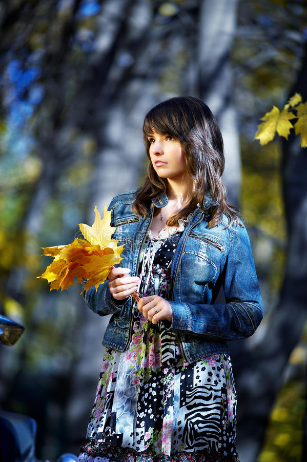 La ragazza con i fogli gialli fotografie stock