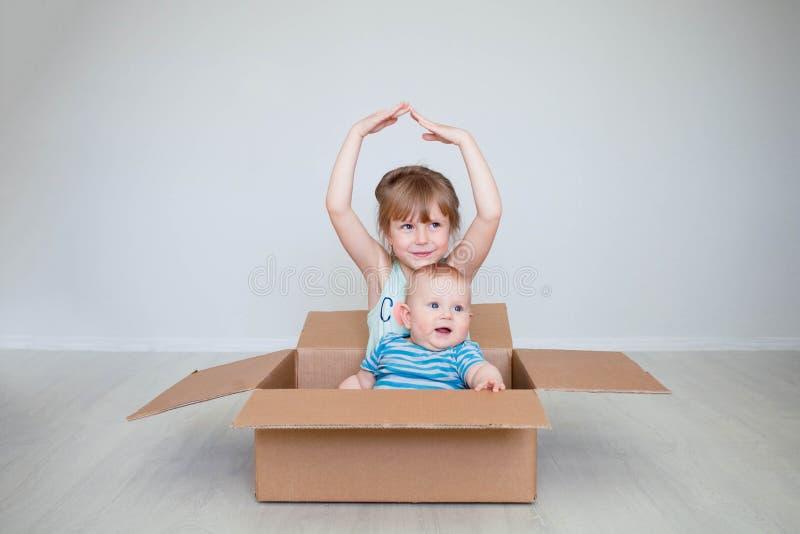 La ragazza con il fratello piccolo si siede in una scatola, il concetto di muoversi rappresenta le mani il tetto immagine stock
