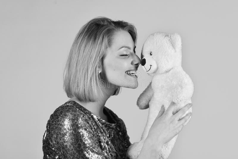 La ragazza con il fronte felice gioca con il giocattolo molle bianco Concetto grazioso di tenerezza e del giocattolo Signora con  immagine stock