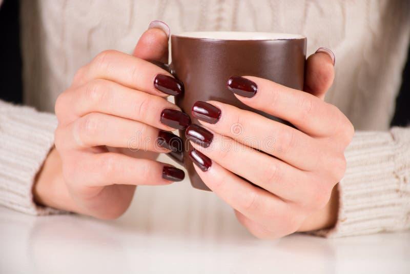La ragazza con il manicure marrone delle unghie tiene la tazza di caffè sullo scrittorio immagini stock