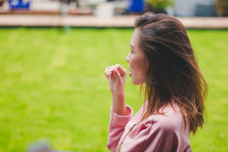 La ragazza con il vento che soffia i suoi capelli fotografia stock