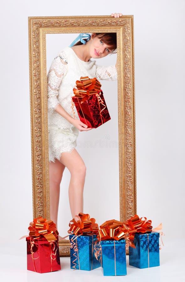 La ragazza con la casella con il regalo sta dietro il blocco per grafici della scrofa giovane immagine stock libera da diritti