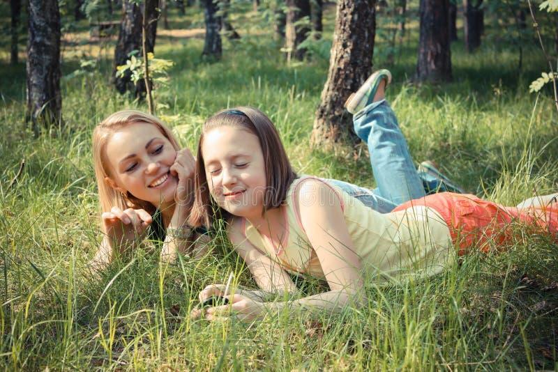 La ragazza con la sua mamma si rilassa in parco fotografia stock libera da diritti