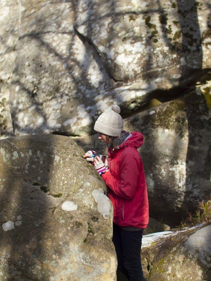 La ragazza con la tazza sta vicino alle pietre immagine stock libera da diritti