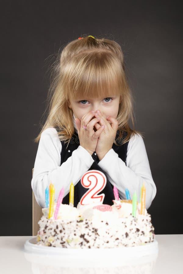La ragazza con la torta di compleanno fa il desiderio immagine stock libera da diritti