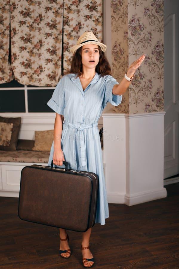 La ragazza con la valigia dà una mano fotografie stock