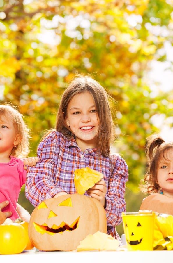 La ragazza con le sorelle scolpisce le zucche per Halloween immagine stock libera da diritti