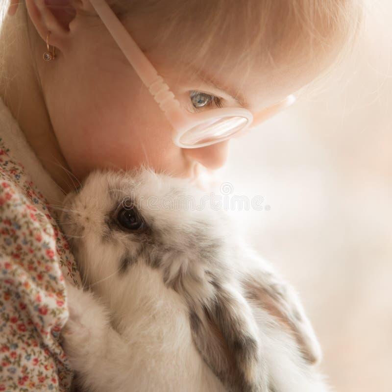 La ragazza con sindrome di Down abbraccia il coniglio immagini stock libere da diritti