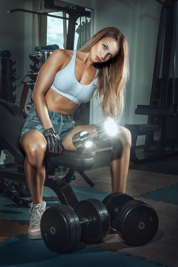 La ragazza con sport calcola i muscoli di scosse immagine stock