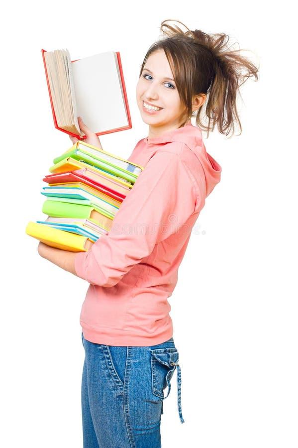 La ragazza con un mucchio dei libri fotografia stock