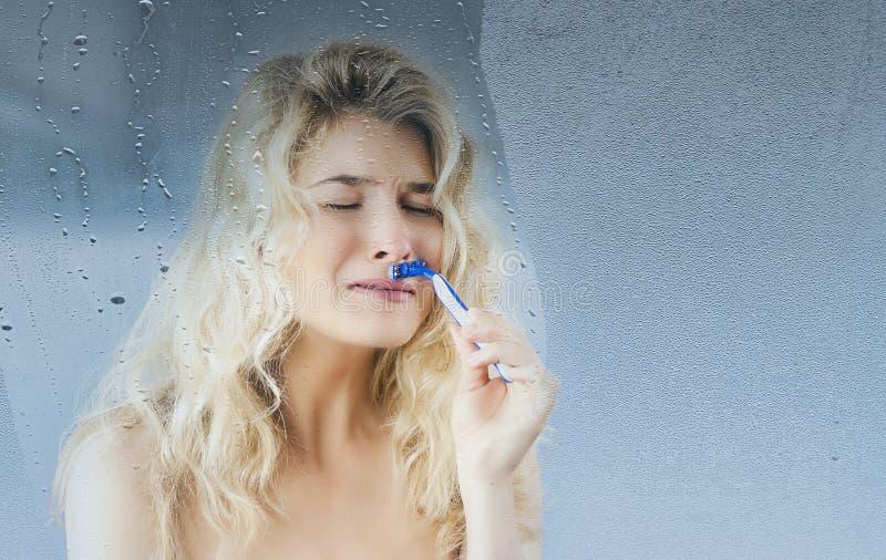 La ragazza con un rasoio a disposizione si rade dopo la presa della doccia su un fondo Bellezza di concetto e cura di pelle fotografie stock libere da diritti