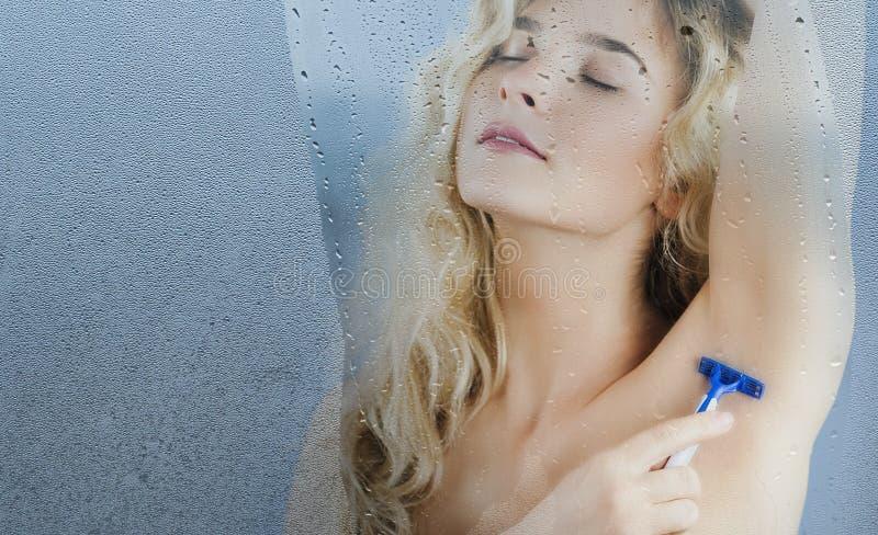 La ragazza con un rasoio a disposizione si rade dopo la presa della doccia su un fondo isolato Bellezza di concetto e cura di pel fotografia stock libera da diritti
