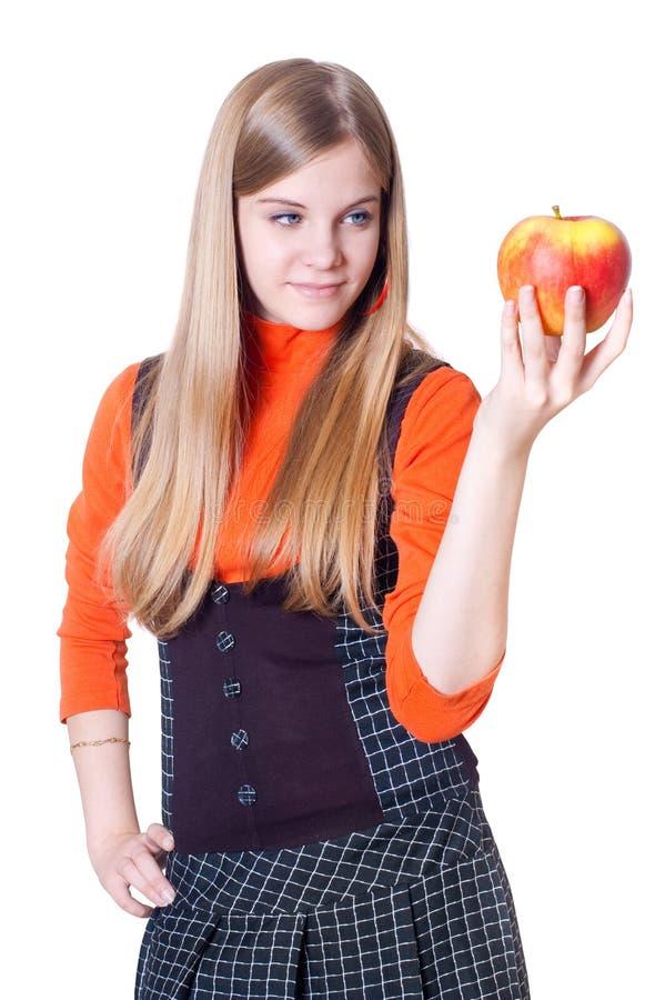 La ragazza con una mela in una mano immagini stock