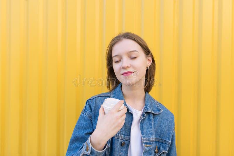La ragazza con una tazza di caffè in sue mani ha chiuso i suoi occhi da piacere ai precedenti della parete gialla fotografie stock libere da diritti