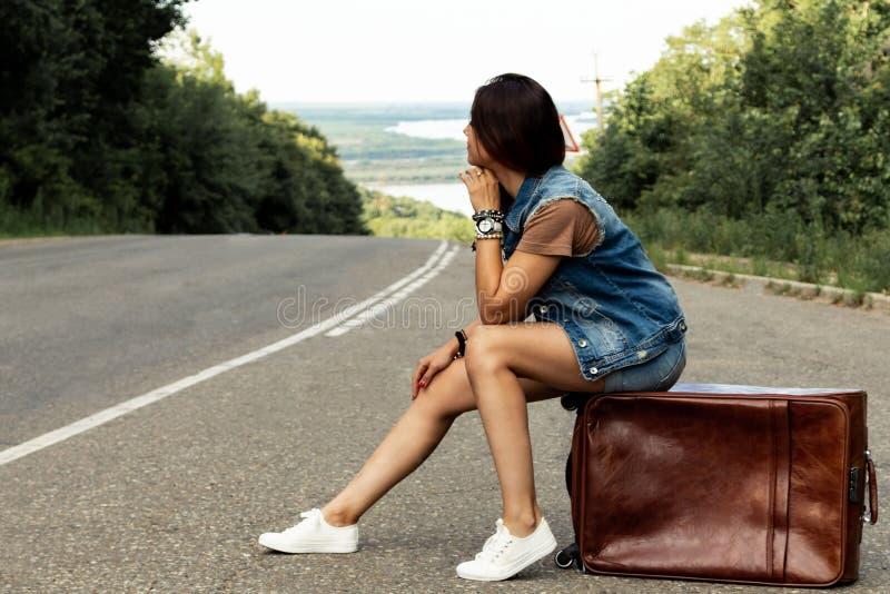 La ragazza con una valigia ferma l'automobile sulla strada fotografie stock